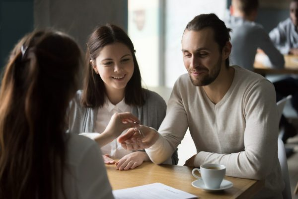 Happy millennial couple getting keys to new house from realtor in cafe, young customers, renters or tenants make real estate deal meeting agent, mortgage loan investment, property ownership concept