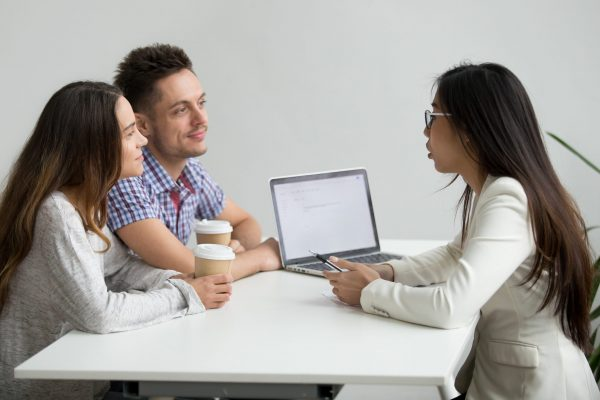 Smiling millennial couple listening to asian realtor, lawyer, bank worker, insurance broker or financial advisor consulting customers planning mortgage loan investment or real estate rent purchase